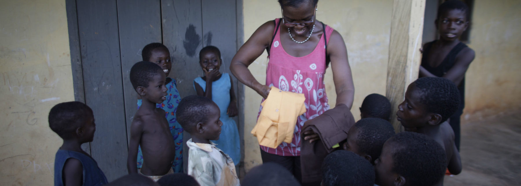 Akosua giving school uniform to children